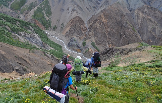 Scouts descend into a steep river carved valley in the Yukon Territory